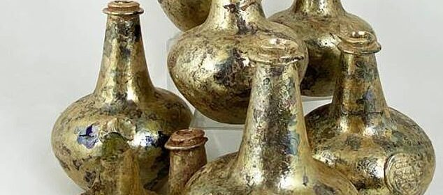 After being discovered by accident at a construction site, a hoard of gold-encrusted 17th century wine bottles is scheduled to go to auction with a guide price of £20,000.